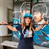 Female model wearing Hertl t-shirt with hockey stick