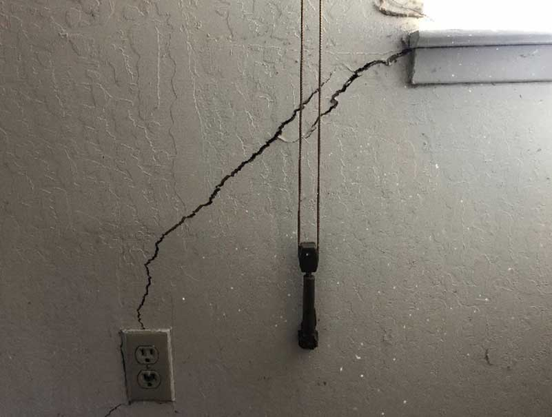 wall crack from outlet to window sill caused by foundation settlement issues