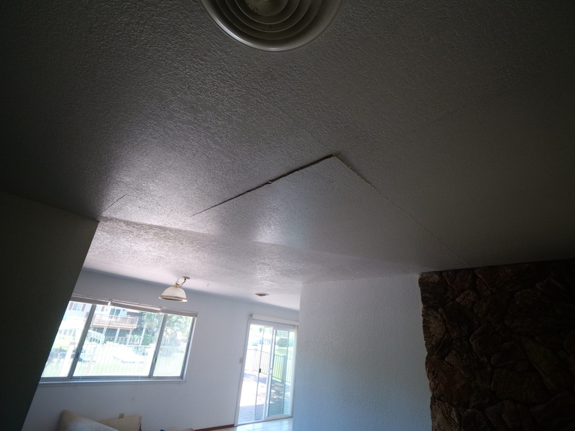 living room with a foundation crack on the ceiling