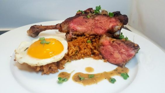 Roasted duck leg with Schwammerlsauce, served alongside Spanish spicy red rice
