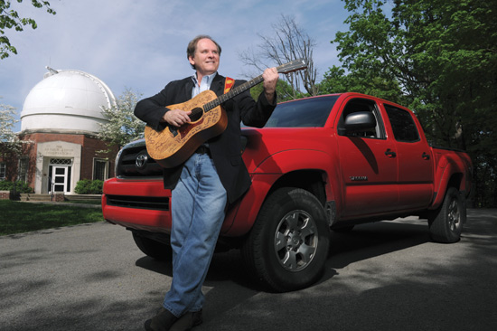Man with guitar and truck.
