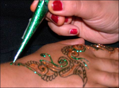 Mad About Music photo gallery image. Having a sparkly henna tattoo applied