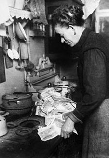 A woman lighting her stove using money