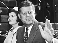 Senator John F Kennedy sits atop a car with his wife Jacqueline Kennedy, waving during a parade moving along Broadway, New York City (19 October 1960)