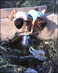 Niños jugando con agua estancada