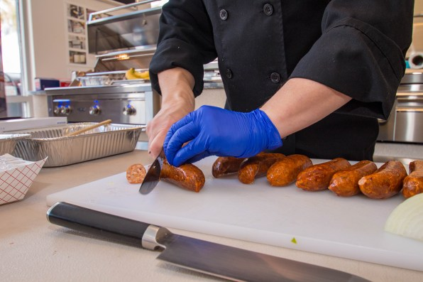 Chef Phillip Dell Cuts Andouille Sausage for Mardi Gras Themed Grilling Class