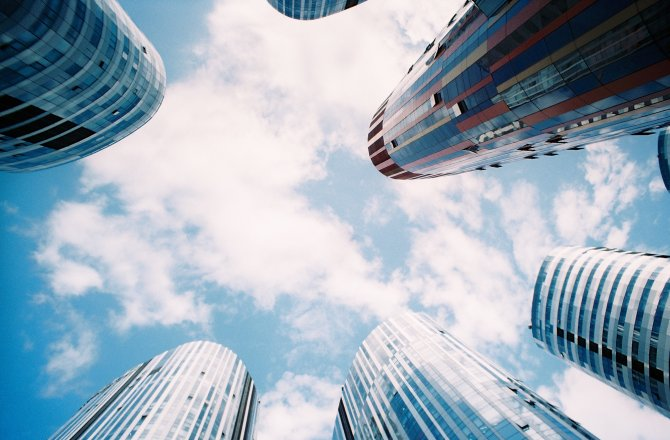 Wolkenkratzer vor blauem Himmel mit Wolken aus Ameisenperspektive