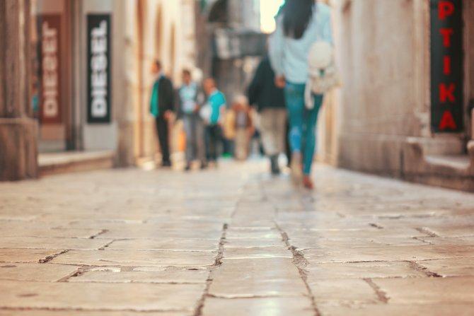 Frau von hinten auf Straße, in Ameisenperspektive