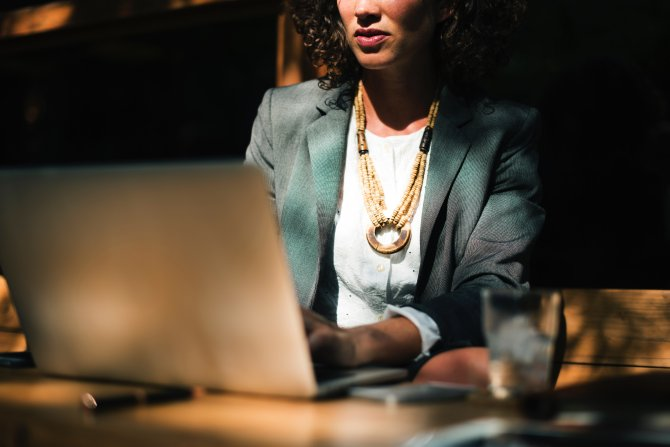 Frau sitzt am Laptop, arbeitet