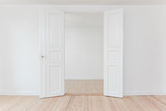 Weiße Flügeltüre vor weißer Wand, geöffnet