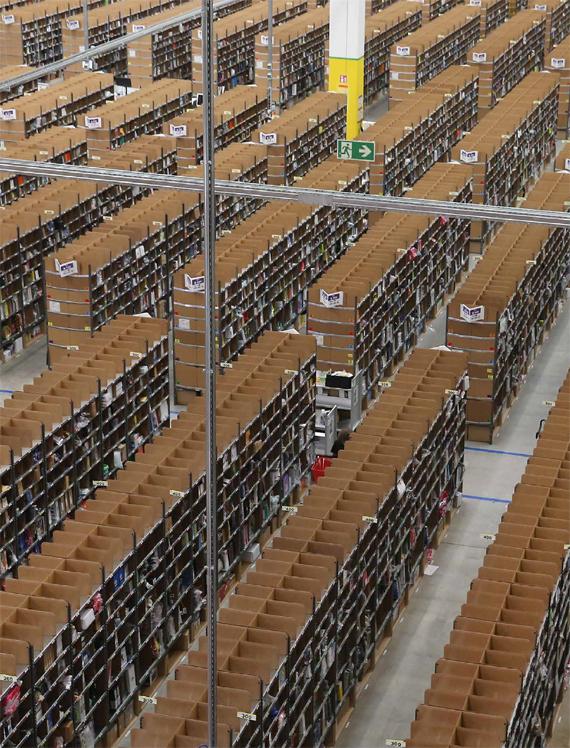 Trabajadores entre estantes con artículos en un almacén de Amazon, en Brieselang, Alemania, el segundo mercado online más importante de Amazon después de EEUU