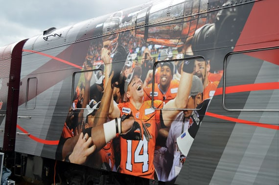 Travis Lulay hoists the cup on the side of the Grey Cup train. - Photo: BCLionsDen.ca