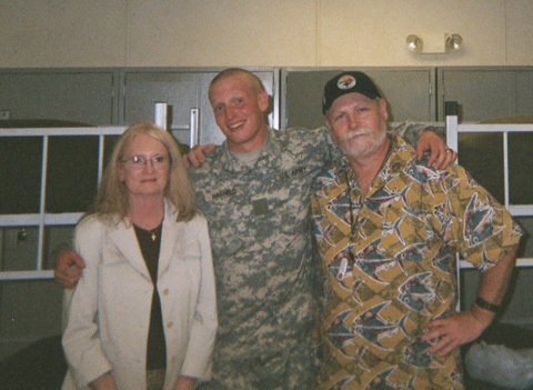 Private Brendan Hatfield poses with his proud parents at his graduation from Basic Combat Training in Fort Jackson, S.C.  Private Hatfield is a 2002 Graduate of George Mason High School and life-long resident of the City of Falls Church. This picture was taken Sept. 21, 2006 in the barracks bay of 1st Platoon, Company E (Death Dealers), 3rd Batallion, 60th Infantry (River Raiders), United States Army at Fort Jackson, S.C. Private Hatfield is currently assigned to Advanced Individual Training at Fort Eustis, VA with the 1st Batallion 222nd Aviation Regiment where he is in training for Blackhawk helicopter (UH-60) repair. (L-R) Kristi Hatfield, Pvt E1 Brendan Hatfield USA, Chris Hatfield.