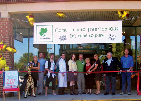 The opening of a new store, Tree Top Kids, held a ribbon cutting ceremony on Saturday, September 29. Holding the shears is manager, Kristen English. (Photo: Courtesy of Sally Cole)