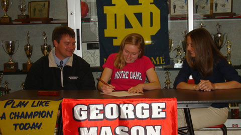 MASON HIGH'S Susanna Sullivan sits with Athletic Director Tom Horn and cross country coach Julie Bravin as she signs her letter committing to Notre Dame. (Photo: Mary Lynn Hickey)