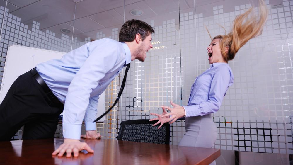 A male boss is creating a hostile work environment by screaming at a female subordinate so loudly her hair stands straight up.