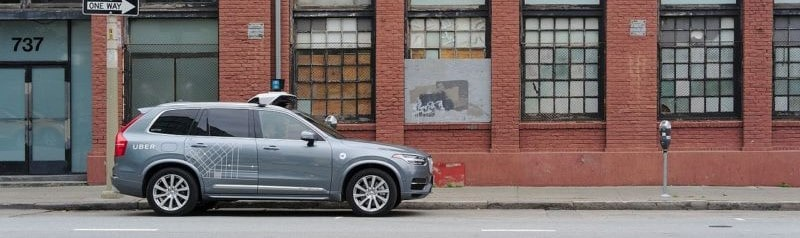 An uber self-driving car is shown on a city street.