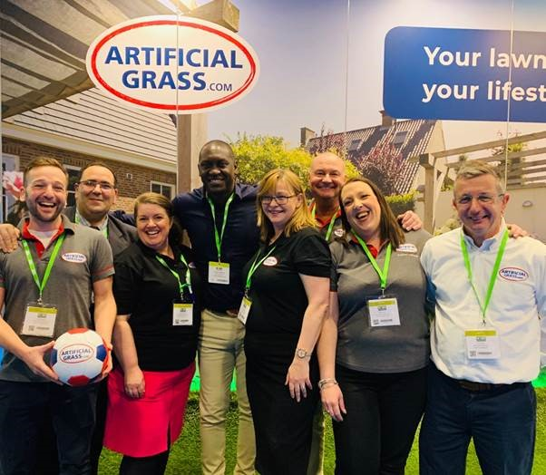 An England football legend has helped ArtificialGrass.com greet visitors to its display at a major industry event held in Coventry.