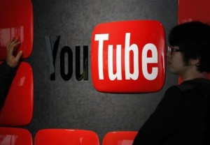 Visitors stand in front of a logo of YouTube at the YouTube Space Tokyo, operated by Google, in Tokyo February 14, 2013.