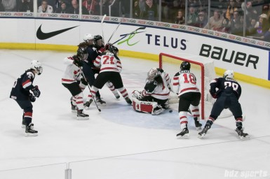The puck slips by Canada's Shannon Szabados #1 and is loose in front of the net during OT.