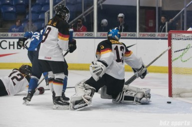 Finland's Noora Tulus #24 beats Germany's Ivonne Schroder #13 to score Finland's fifth goal of the game.