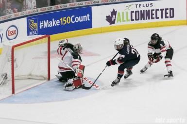 Canada's Shannon Szabados #1 poke checks USA's Alex Carpenter #25.