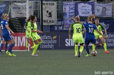 Breakers' Rosie White #10 takes a shot while Reign FC players look on.
