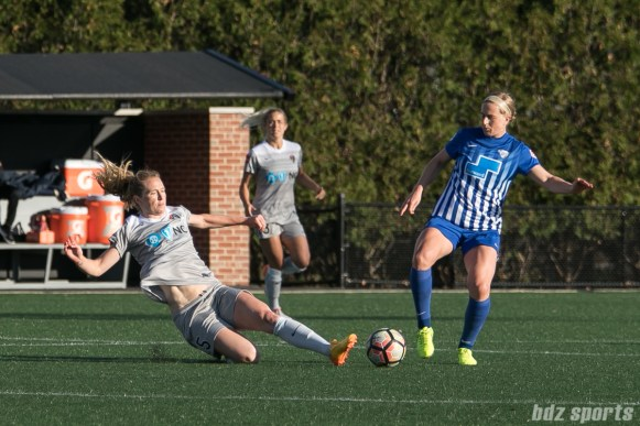 Courage's Sam Mewis #5 goes in for the slide tackle against the Breakers' Natasha Dowie #9.