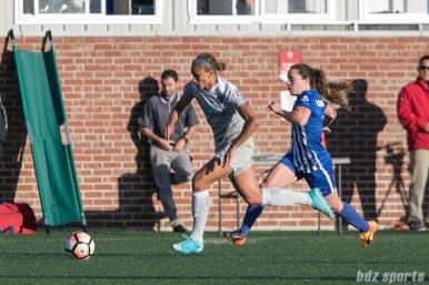 Courage's Lynn Williams #9 brings the ball down field while the Breakers' Allysha Chapman #2 gives chase.