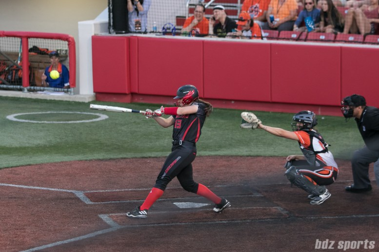 Akron Racers catcher Griffin Joiner (13) makes contact with the ball.