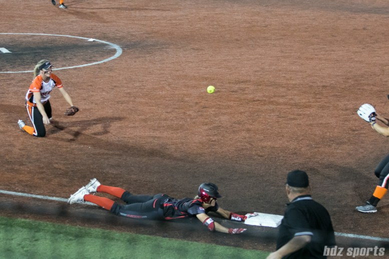 Akron Racers outfielder Jennifer Gilbert (25) slides to beat out the throw to first by Chicago Bandits first baseman Chelsea Forkin (25) .