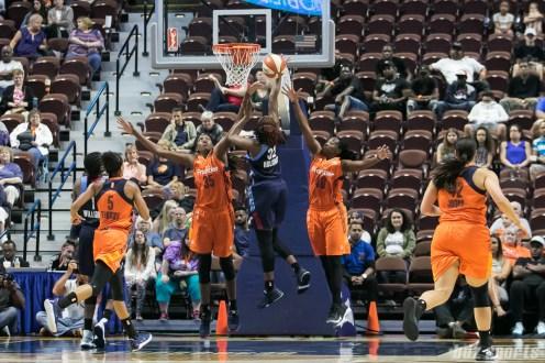Connecticut Sun center Jonquel Jones (35) and forward Shekinna Stricklen (40) look to block the layup of Atlanta Dream guard Bria Holmes (32).
