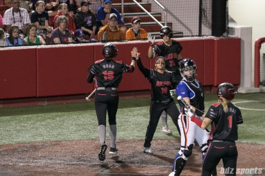 Akron Racers second baseman Alex Hugo (16) high fives third baseman Kelley Montalvo (10) after scoring a run.