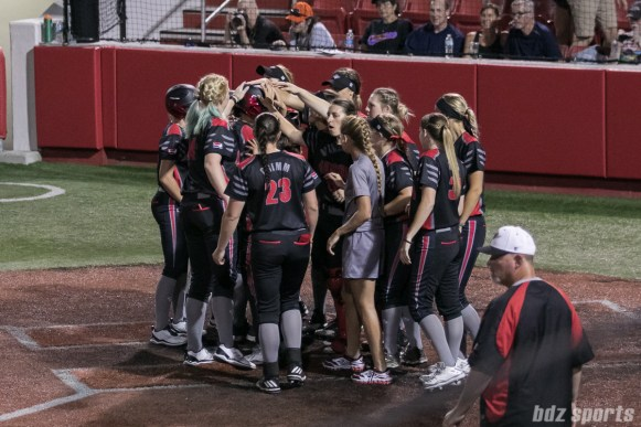 The Akron Racers swarm teammate Alex Hugo after her solo home run.