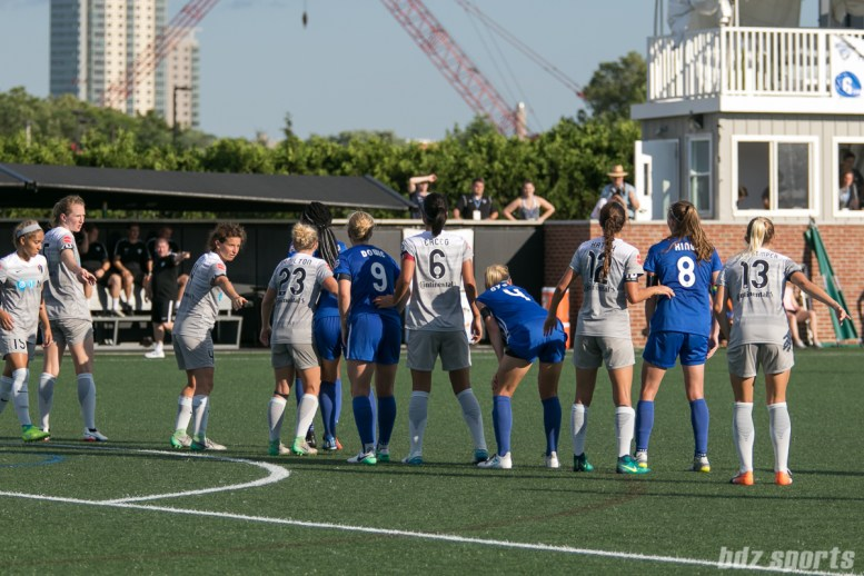 Players on the North Carolina Courage and Boston Breakers prepare for a Breakers' free kick.