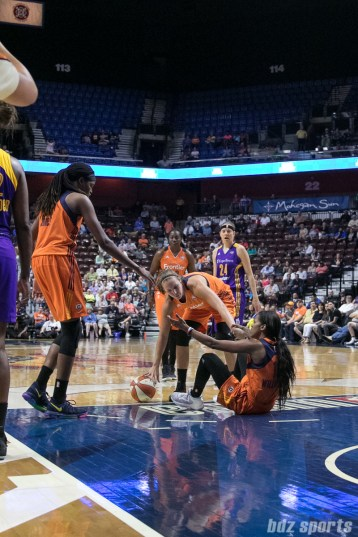 Connecticut Sun guard Courtney Williams (10) is helped up by teammates Jonquel Jones (35) and Kayla Pedersen (7).