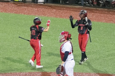 Akron Racers third baseman Kelley Montalvo (10) high fives teammate A.J. Andrews (9) after scoring a run in the third inning.