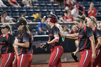 Akron Racers infielder Sam Fischer (52) is all smiles after hitting her solo home run.