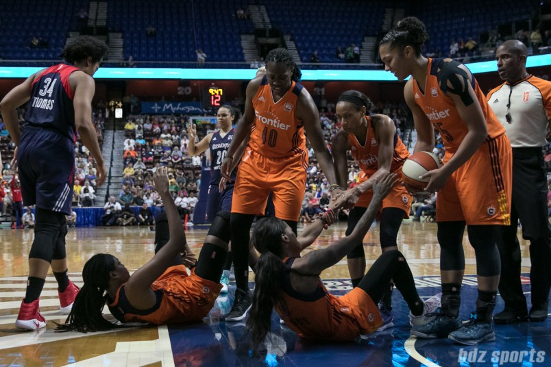 Connecticut Sun teammates Shekinna Stricklen (40), Jasmine Thomas (5), and Alyssa Thomas (25) help Jonquel Jones (on the ground left) and Courtney Williams (on the ground right) off the ground.