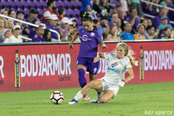 FC Kansas City forward Brittany Ratcliffe (25) slide takcles the ball away from Orlando Pride defender Camila Pereira (9).