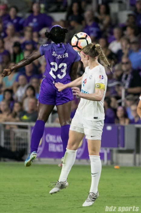 FC Kansas City defender Becky Sauerbrunn (4) gets her head on the ball while being challenged by Orlando Pride forward Jasmyne Spencer (23).