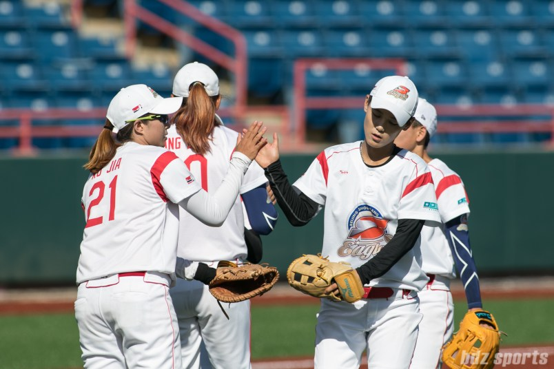 The Beijing Eagles infielders high five before taking their places.