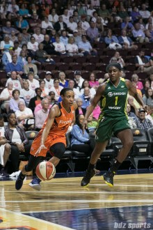 Connecticut Sun guard Jasmine Thomas (5) drives to the basket past Seattle Storm forward Crystal Langhorne (1).
