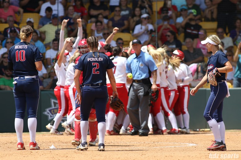 The USSSA Pride infielders gather at the mound as the Scrap Yard Dawgs celebrate a home run in the background