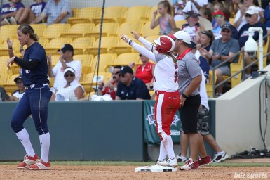 Scrap Yard Dawgs Kasey Cooper (31) signals to the Dawgs' dugout after she advances to third base