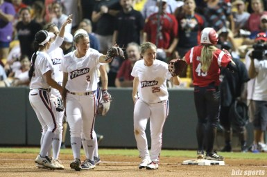 The USSSA Pride point to outfielder Kirsti Merritt (not pictured) after her throw helped get the out at third base
