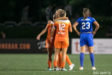 Houston Dash forward Rachel Daly (3) hugs teammate Camille Levin and Amber Brooks after the Dash defeat the Breakers 3 - 1