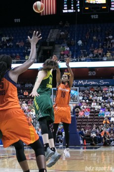Connecticut Sun guard Courtney Williams (10) releases a 3-point shot over the hand of Seattle Storm forward Breanna Stewart (30).