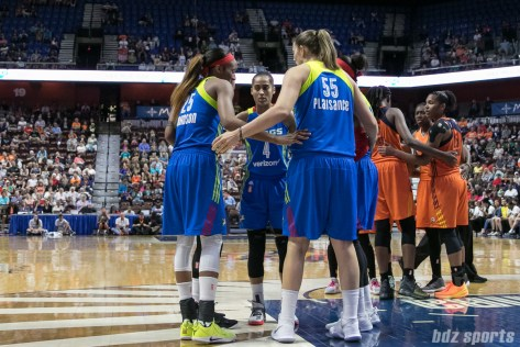 The Dallas Wings and Connecticut Sun huddle during a stop in play.