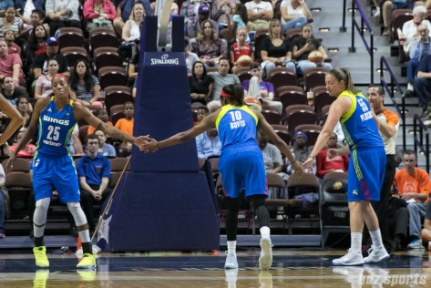 Dallas Wings forwards Glory Johnson (25) and Theresa Plaisance (55) high five teammate Kaela Davis (10) in between foul shots.